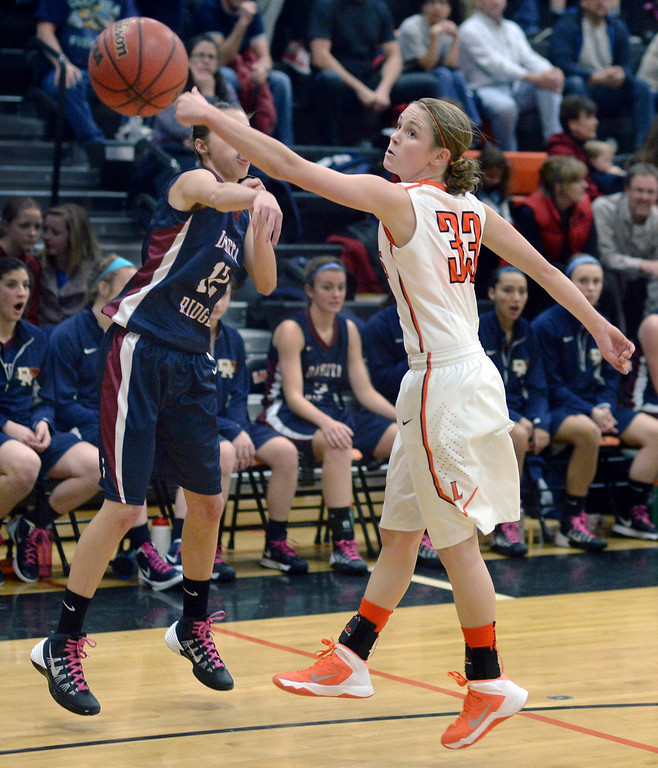 . Lakewood sophomore guard Mackenzie Forrest (33) knocked away a pass from Dakota Ridge\'s Sydney Buchli (12) in the first half.  Photo By Karl Gehring/The Denver Post