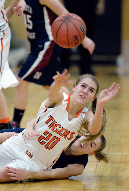 . Lakewood guard Madeline Miller (20) passed the ball forward after winning a race to a loose ball with Dakota Ridge junior Aly Suniga (12) in the first half.  Photo By Karl Gehring/The Denver Post