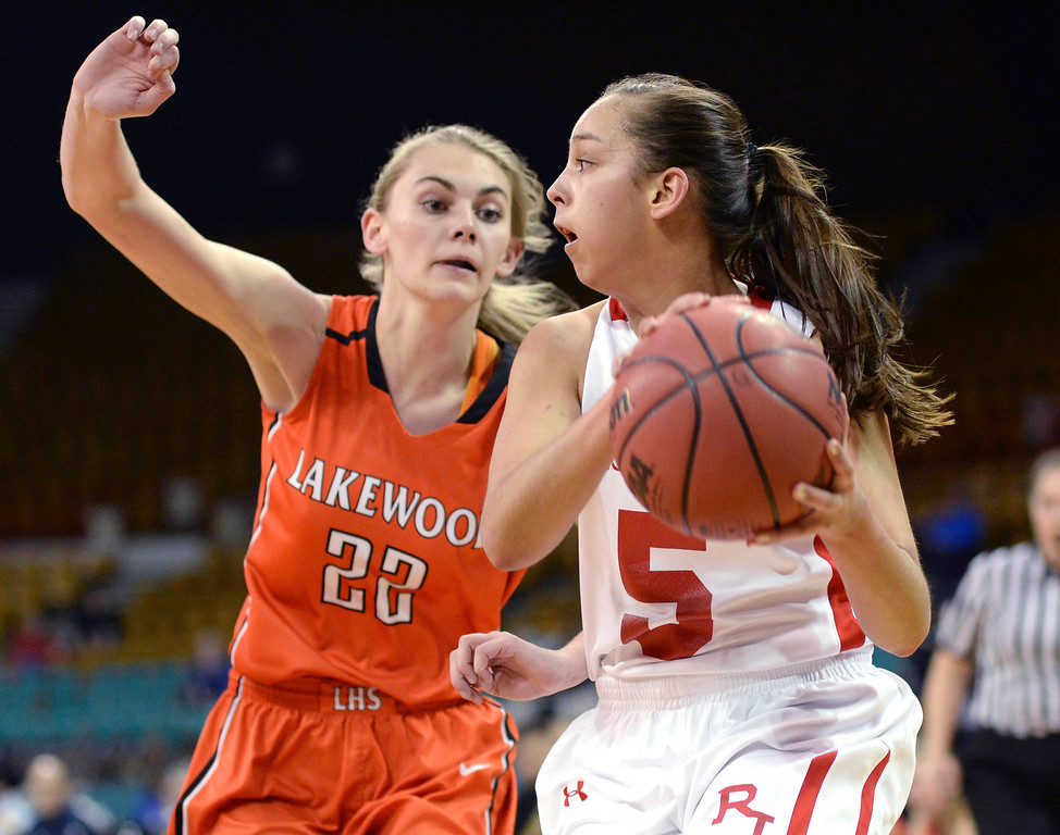 . Regis guard Anna Ptasinksi (5) looked to pass around Lakewood defender McKenna Bishop (22) in the first half. The Regis Jesuit High School girl\'s basketball team faced Lakewood in a 5A playoff game Thursday night, March 6, 2014 in Denver, Colorado. (Photo by Karl Gehring/The Denver Post)
