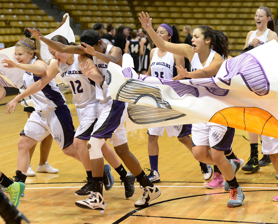 . Mesa Ridge players burst through a banner before the game against Pueblo South High School g in a 4A semifinal game Thursday night, March 13, 2014 in Boulder, Colorado. (Photo by Karl Gehring/The Denver Post)