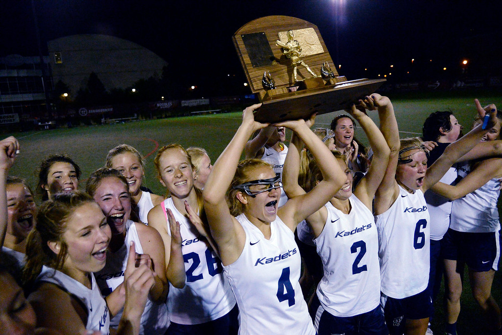 . Jessica Berg (4) of the Air Academy Kadets hoists the championship trophy after Academy\'s 11-10 girls 5A championship game win over the Cherry Creek Bruins.  (Photo by AAron Ontiveroz/The Denver Post)
