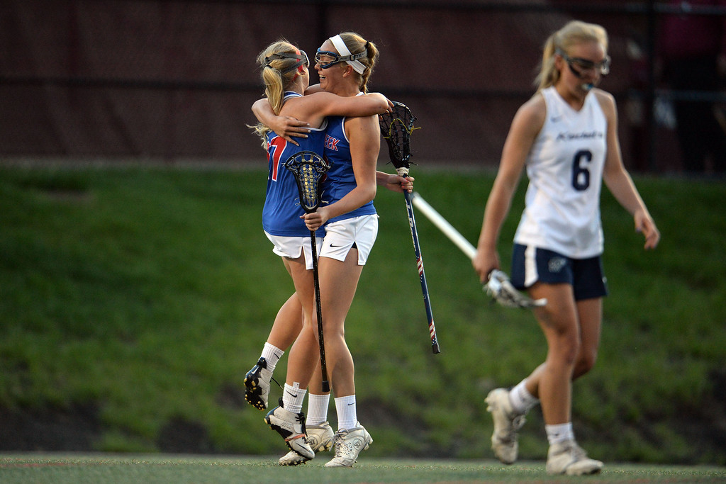 . Annie Dent (27) of the Cherry Creek Bruins and Sarah Cromer (18) hug as Katey Holmes (6) of the Air Academy Kadets reacts to the Bruins\' early lead during Academy\'s 11-10 girls 5A championship game win. (Photo by AAron Ontiveroz/The Denver Post)