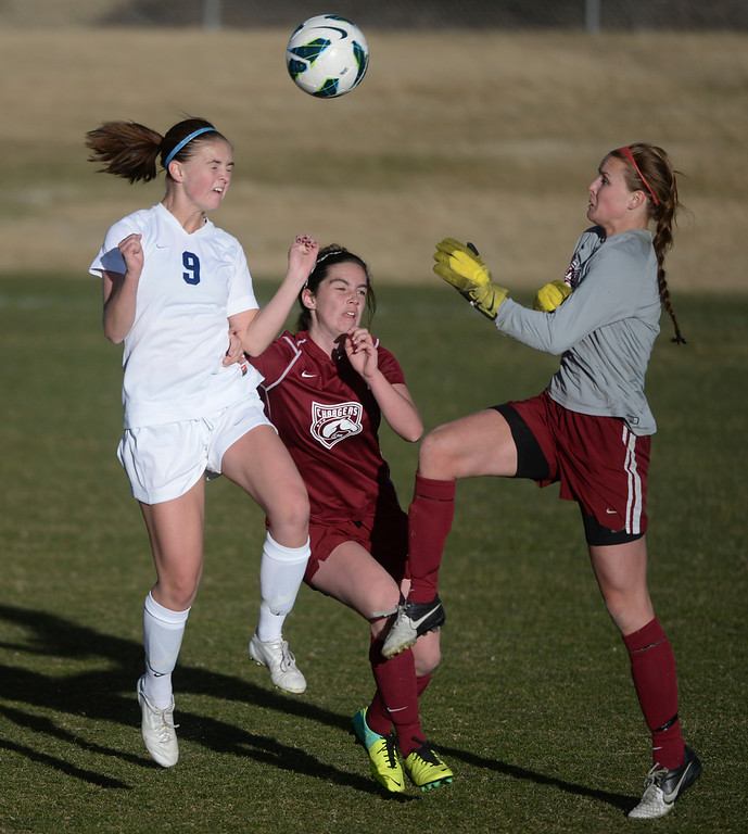 . ARVADA, CO - MARCH 19: Ralston Valley sophomore forward Emma Musson (9) challenged Chatfield goalie Brittany Wilson (0) for the ball with time running out in the second overtime period Wednesday. Musson won the ball and scored the game winning goal. The Ralston Valley High School girl\'s soccer team defeated Chatfield 3-2 Wednesday evening, March 19, 2014. (Photo by Karl Gehring/The Denver Post)