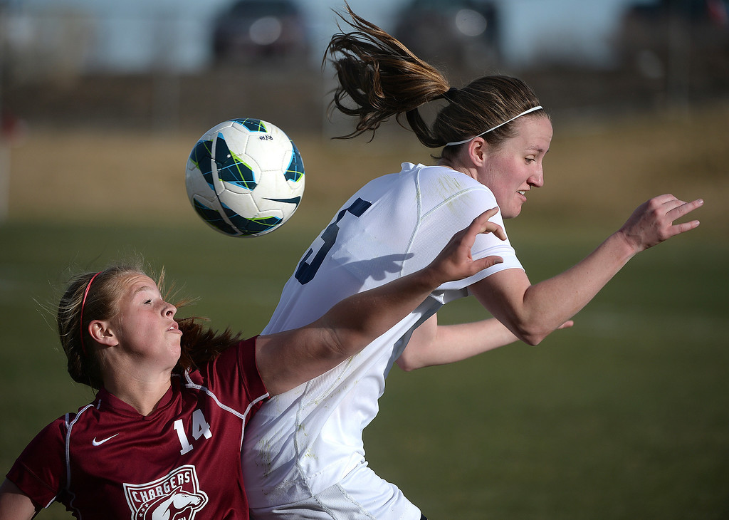. ARVADA, CO - MARCH 19: Chatfield freshman Bree Bezdek (14) challenged Ralston Valley defender Maddie Allensworth (5) in the second half. The Ralston Valley High School girl\'s soccer team defeated Chatfield 3-2 with an overtime goal by sophomore forward Emma Musson Wednesday evening, March 19, 2014. (Photo by Karl Gehring/The Denver Post)