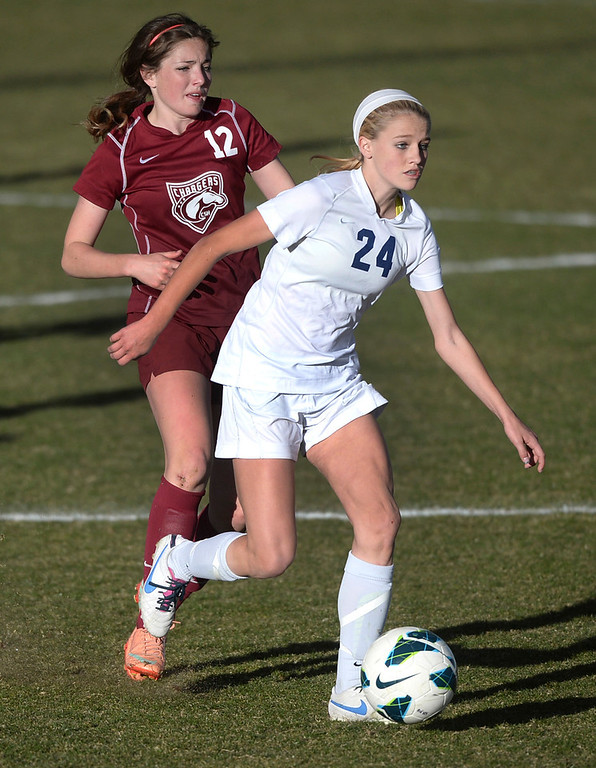 . ARVADA, CO - MARCH 19: Ralston Valley midfielder Alyssa Kaiser (24) raced past Chatfield\'s Carly George (12) in the second half. The Ralston Valley High School girl\'s soccer team defeated Chatfield 3-2 with an overtime goal by sophomore forward Emma Musson Wednesday evening, March 19, 2014. (Photo by Karl Gehring/The Denver Post)