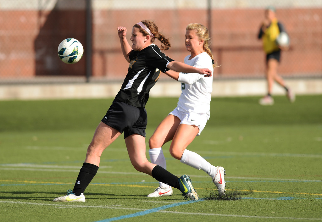 . Amy Alexander of Mountain Vista High School (5), right, and Kelsey Vogel of Arapahoe High School (9) chase a free ball in the first half of the game at Shea Stadium in Highlands Ranch, Colorado on March 29, 2014. Mountain Vista won, 5-4. (Photo by Hyoung Chang/The Denver Post)