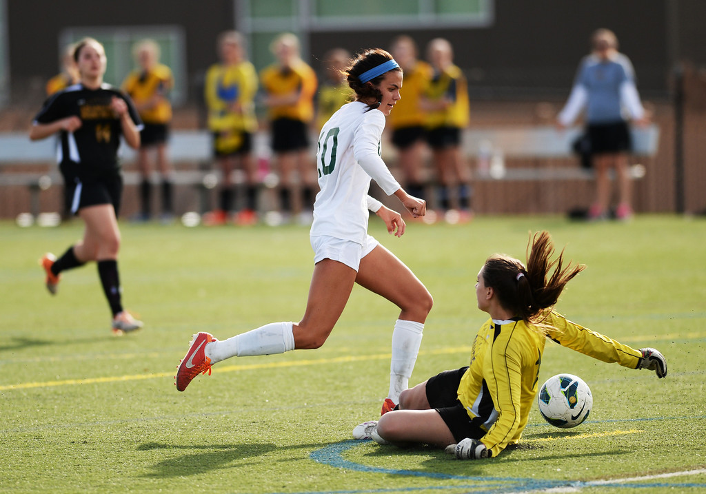 . Megan Massey of Mountain Vista High School (10) scores against Hannah Archuleta of Arapahoe High School (1) in the first half of the game at Shea Stadium in Highlands Ranch, Colorado on March 29, 2014. Mountain Vista won, 5-4. (Photo by Hyoung Chang/The Denver Post)