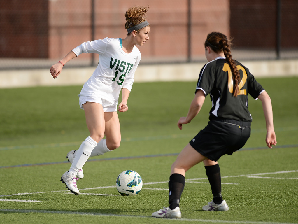 . Kelsey Luke of Mountain Vista High School (19), left, controls the ball against Paige Husa of Arapahoe High School (12) in the first half of the game at Shea Stadium in Highlands Ranch, Colorado on March 29, 2014. Mountain Vista won, 5-4. (Photo by Hyoung Chang/The Denver Post)