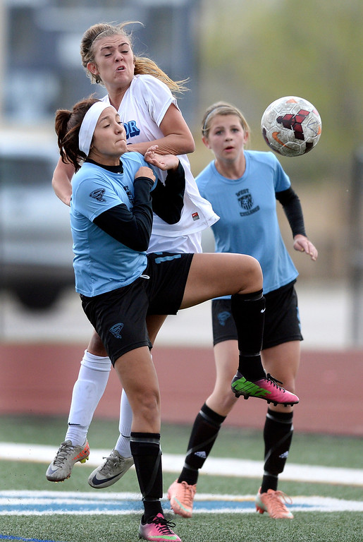 . Cyclones\' senior midfielder Makenzie Olguin (12) and Eagles\' midfielder Gabbi Fleischli (18) competed for the ball on a corner kick in the first half. The Valor Christian High School girl\'s soccer team defeated Pueblo West 4-1Wednesday night, May 7, 2014 in the first round of the playoffs. (Photo by Karl Gehring/The Denver Post)