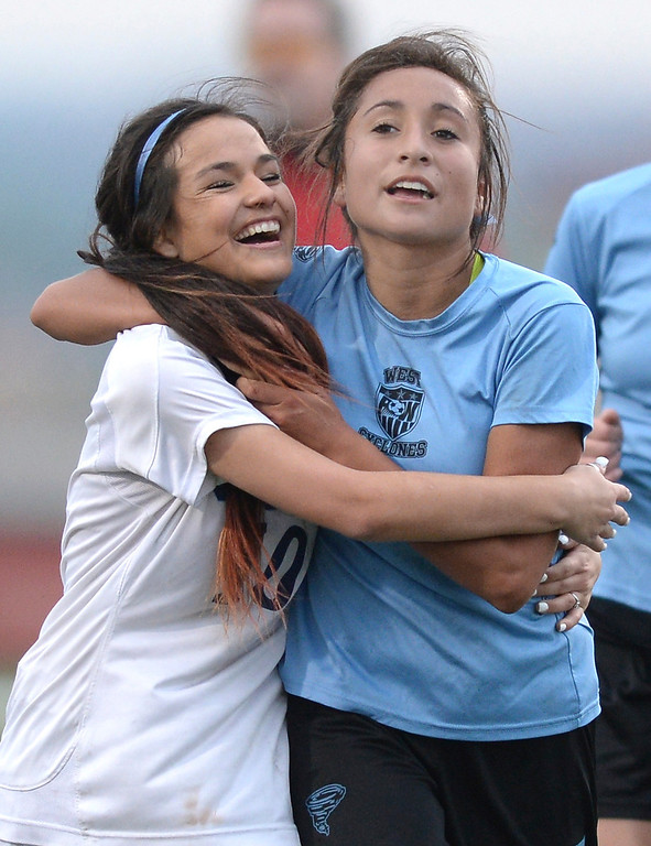 . Friends Amanda Lopez, left, and Deanna Rangel, right, embraced after the contest. The Valor Christian High School girl\'s soccer team defeated Pueblo West 4-1 Wednesday night, May 7, 2014 in the first round of the playoffs. (Photo by Karl Gehring/The Denver Post)