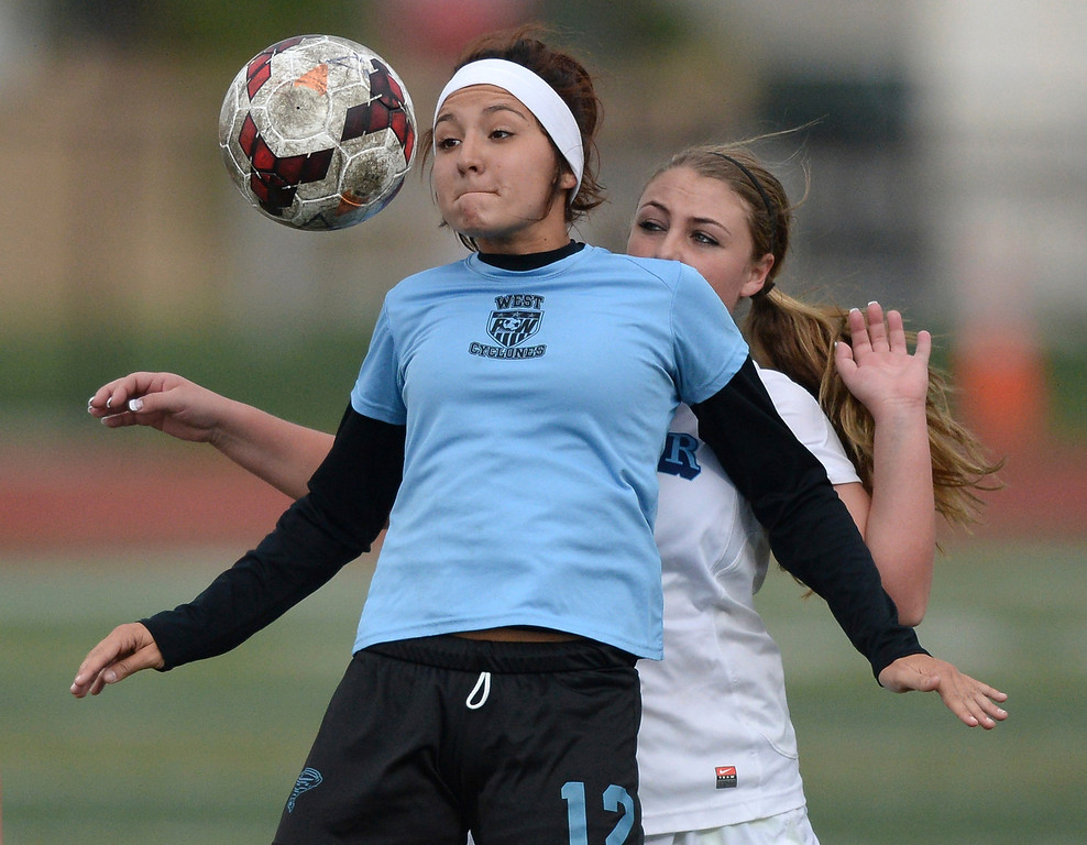 . Pueblo West senior midfielder Makenzie Olguin (12) controlled the ball in front of Valor defender Allie Miller (11) in the second half. The Valor Christian High School girl\'s soccer team defeated Pueblo West 4-1 Wednesday night, May 7, 2014 in the first round of the playoffs. (Photo by Karl Gehring/The Denver Post)