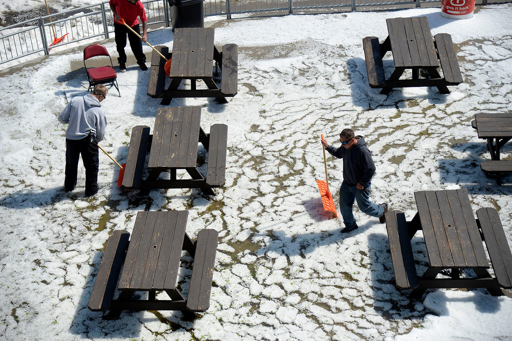 . Grounds crew try to drain the water and hail from the picnic area at Dick\'s Sporting Goods Park. Hail pounded Commerce City blanketing the field at Dick\'s Sporting Goods Park May 21, 2014, where they were about to hold the class 4A soccer finals. (Photo by John Leyba/The Denver Post)