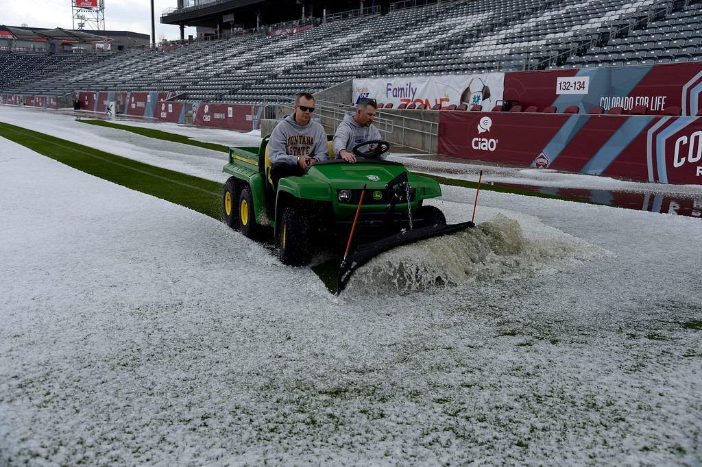 . Cody Witham (L) and Phil McQuade test the turf as they plow a section of the turf at Dick\'s Sporting Goods Park. Hail pounded Commerce City blanketing the field at Dick\'s Sporting Goods Park May 21, 2014 where they were about to hold the class 4A soccer finals. (Photo by John Leyba/The Denver Post)