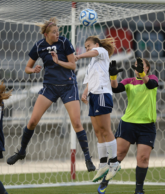 . Columbine junior Amanda Porter, center, got between Ralston Valley defender Sarah Bevington and goalie Renee Roemer for an attempt at heading in a corner kick in the second half. The Columbine High School girl\'s soccer team defeated Ralston Valley 3-1 in the 5A championship game Thursday night, May 22, 2014.  (Photo by Karl Gehring/The Denver Post)