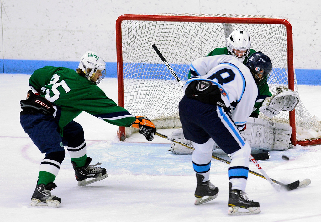 . Ralston Valley senior forward Chris Rockers (8) fired on Standley Lake goaltender Ryan Young (1) in the second period. The defending state champion hockey team from  Ralston Valley High School took on Standley LakeTuesday night, December 17, 2013. Photo By Karl Gehring/The Denver Post