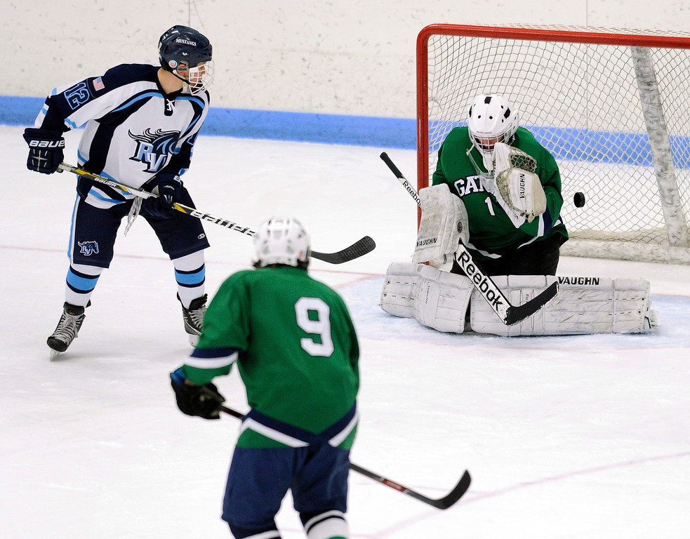 . Ralston Valley senior forward Victor Lombardi (12) tried to flip the puck past Gators\' goalie Ryan Young (1) in the second period. The defending state champion hockey team from  Ralston Valley High School took on Standley LakeTuesday night, December 17, 2013. Photo By Karl Gehring/The Denver Post