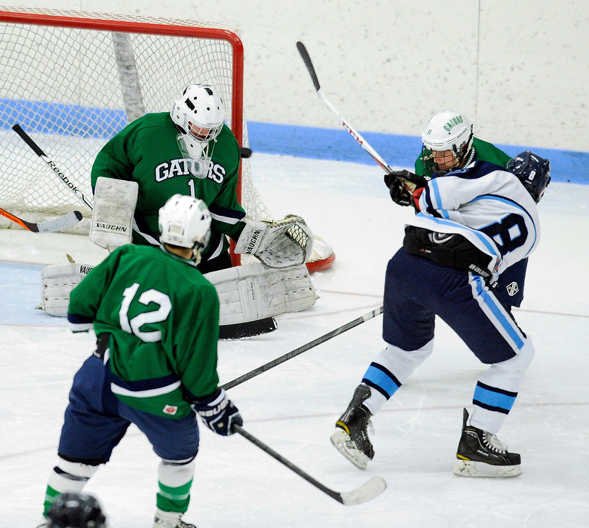 . Ralston Valley forward Chris Rocker (8) found a space between Gators\' goaltender Ryan Young and the pipe in the second period to make the score 2-1. The defending state champion hockey team from Ralston Valley High School took on Standley LakeTuesday night, December 17, 2013. Photo By Karl Gehring/The Denver Post