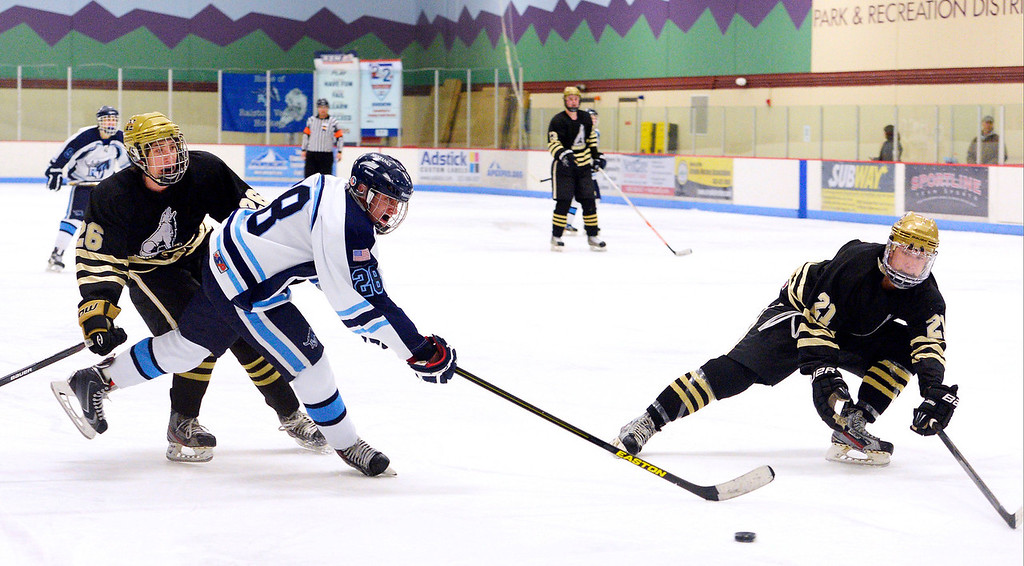 . Ralston Valley Hunter Schoepflin (28) trie sot get a shot off during the second period as Monarch Ryan Uhland (26) and Drew Wagner come in on defense January 14, 2014 at Apex Ice Arena. (Photo by John Leyba/The Denver Post)