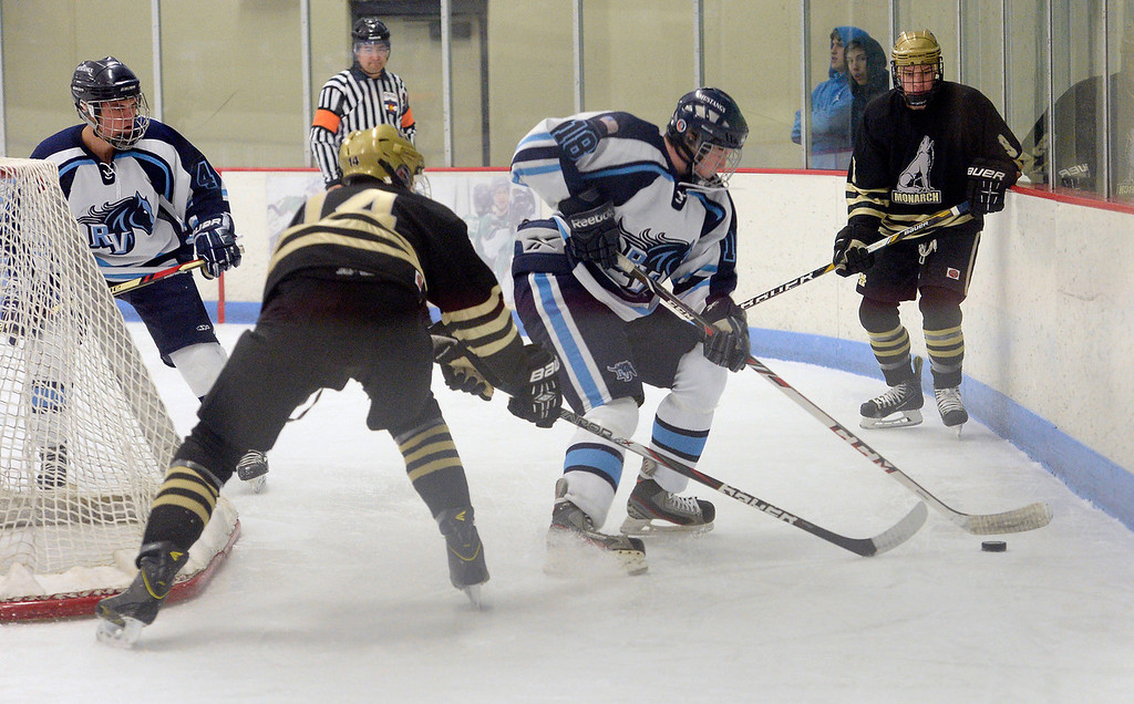 . Ralston Valley Martin Bakula (18) works the puck behind the goal as Monarch Adam Tybor  (14) comes in on defense during the first period January 14, 2014 at Apex Ice Arena. (Photo by John Leyba/The Denver Post)
