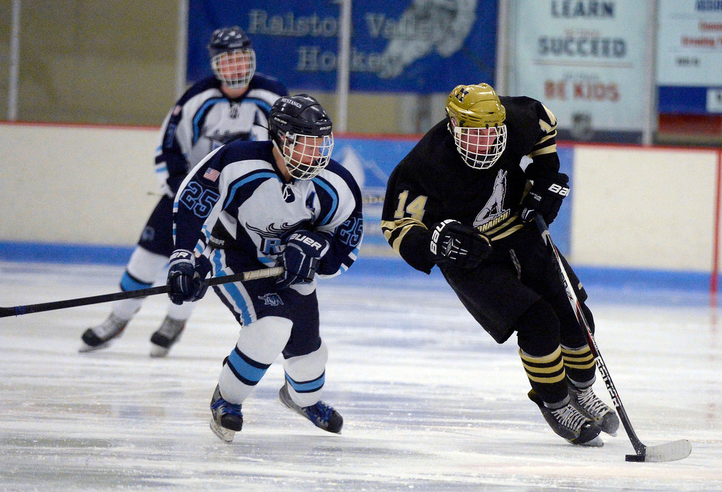 . Monarch Adam Tybor (14) skates the puck as he gets chased by Ralston Valley Nick Wiemelt (25) during the third period January 14, 2014 at Apex Ice Arena. (Photo by John Leyba/The Denver Post)