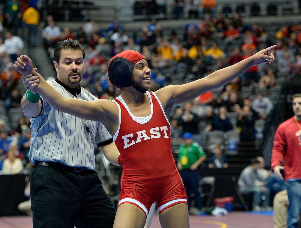 . Maya Nelson of Denver East points to family and friends in the stands after her 13-9 win over Carl Camposanto of Regis during their 5A 106-pound match on the first day of Colorado High School State Wrestling February 20, 2014 Pepsi Center. (Photo by John Leyba/The Denver Post)