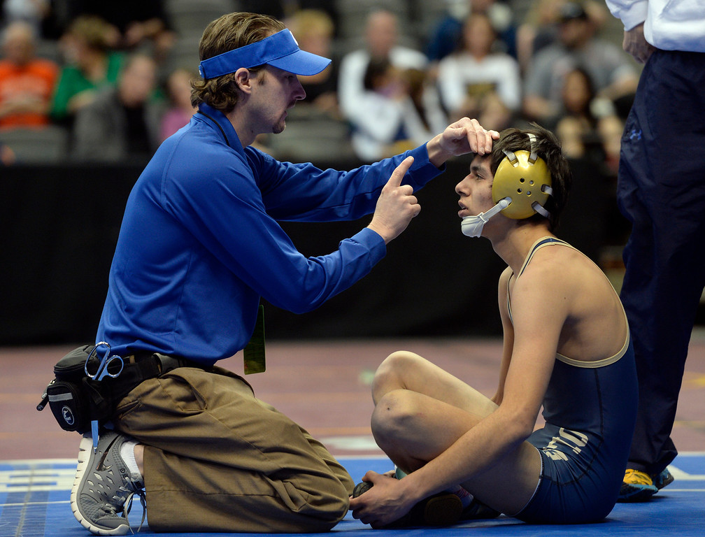 . DENVER, CO - FEBRUARY 21: After falling hard on his back and hitting the mat with his head, a doctor checks Emmanuel Barba from Olathe for signs of a concussion. The Colorado Wresting State Championships take place at the Pepsi Center with the quarterfinals taking place on Friday, Feb. 21, 2014. (Photo by Kathryn Scott Osler/The Denver Post)