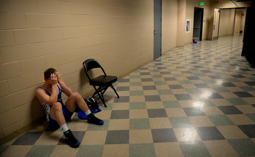 """. DENVER, CO. - FEBRUARY 22: Senior Drake Greeott of Longmont High School sits in the hallway after his loss in the Colorado State Wrestling Championship at the Pepsi Center in Denver, CO February 22, 2014. Greeott said he started strong in the 4A 160-pound consolation match, \""""then he got a couple of back points and I got a couple of stalling calls... it\'s hard.\"""" (Photo By Craig F. Walker / The Denver Post)"""