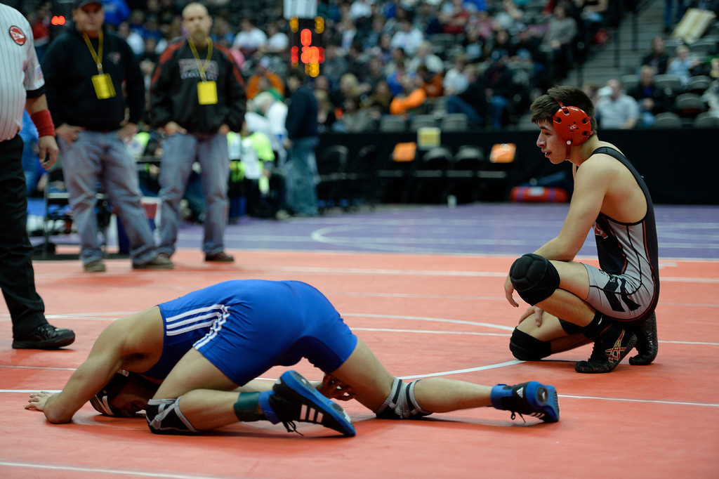 . DENVER, CO - FEBRUARY 20: Sergio Chavez of Hinkley (L) grimaces as he grabs his right knee during his match with Jason Romero of Pomona in class 5A 132 pound match on the first day of Colorado High School State Wrestling February 20, 2014 Pepsi Center. The match was stopped as Chavez couldn\'t continue with his knee injury. (Photo by John Leyba/The Denver Post)