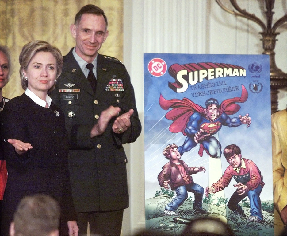 . First lady Hillary Rodham Clinton, accompanied by Lt. Gen. Michael Davison, unveils a Superman comic book in the Roosevelt Room of the White House Monday, Aug. 2, 1999 to promote awareness of land mines in Kosovo. More than 200 accidents involving mines and unexploded ordnance have occurred. (AP Photo/Khue Bui)