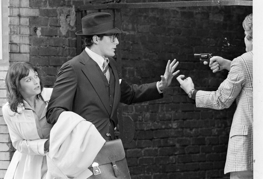 ". Clark Kent, aka Superman portrayed by Christopher Reeve, raises his hand as he and Lois Lane, portrayed by Margot Kidder, left, are mugged by an armed man in an alleyway in the Lower East Side during a scene from ""Superman\"" filmed in New York City, Friday, July 8, 1977.  (AP Photo)"