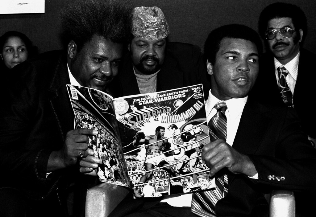 . World heavyweight champion Muhammad Ali, right, is shown at a press conference in New York, January 31, 1978, with promoter Don King, left, and Herbert Muhammad, center, to plug a comic book in which he beats Superman.  Ali holds a copy of the comic book.  (AP Photo/Marty Lederhandler)