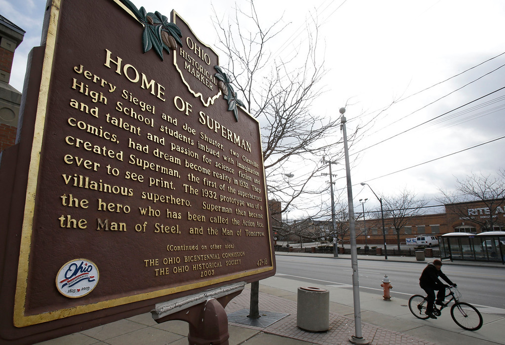 . In this Tuesday, April 2, 2013 photo shows a man riding his bicycle past the Home of Superman plaque in Cleveland. Superman collaborators Jerry Siegel and Shuster lived several blocks apart in the Glenville neighborhood which shaped their lives, dreams for the future and their imagery of the Man of Steel. (AP Photo/Tony Dejak)