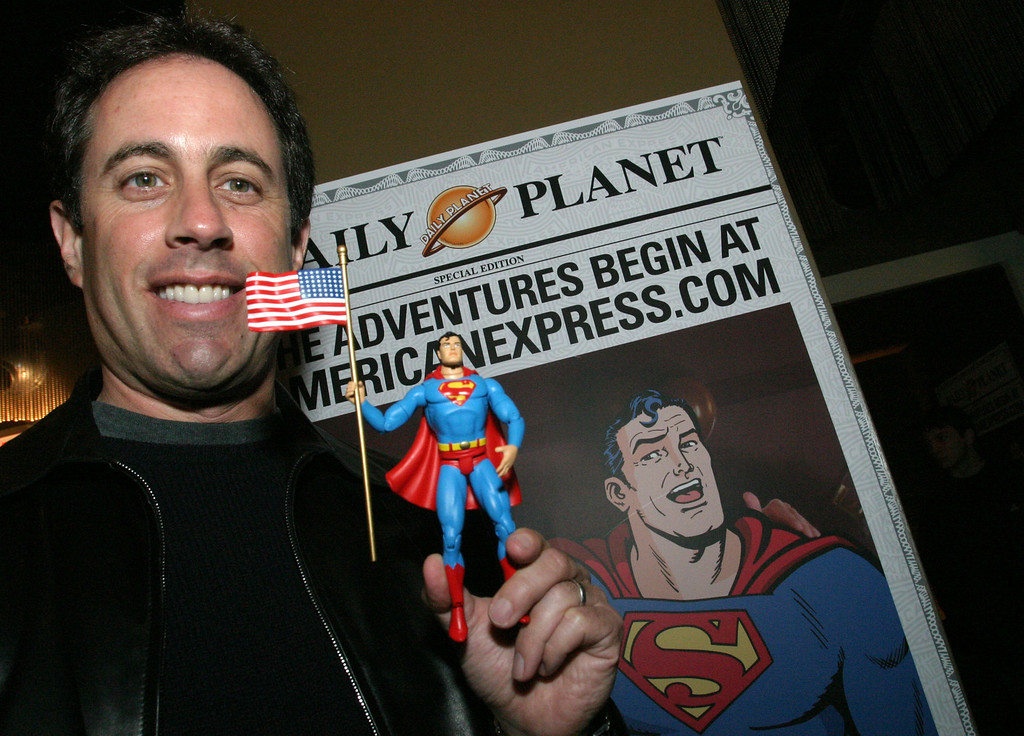 ". Comedian Jerry Seinfeld poses with a Superman action figure after  unveiling American Express\'  Superman ""webisode\"" at W Hotel in New York on Monday, March 29, 2004. The five minute episode, which is appearing on the company\'s website, is directed by Barry Levinson and stars Seinfeld and SuperMan. (AP Photo/Tina Fineberg, American Express )"