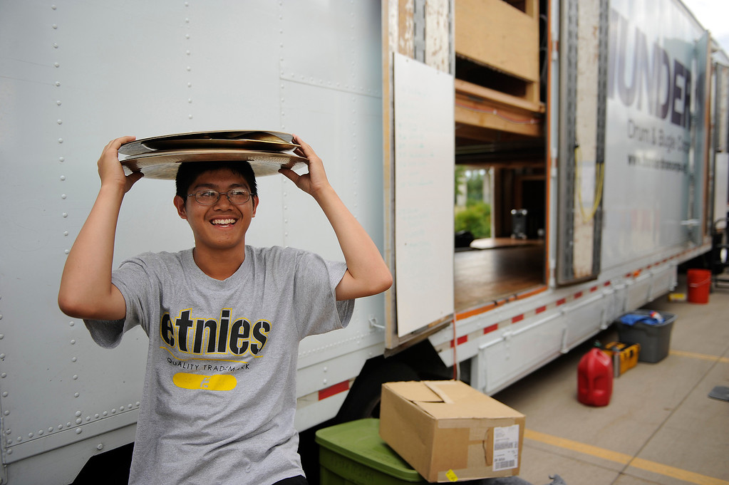 . DENVER, CO. - JULY 6:  Percussionist Austin Nguyen unloaded cymbals from a trailer Saturday afternoon. The nation\'s top drum and bugle corps entertained a crowd and battled for top honors at the Drums Along the Rockies competition at Sports Authority Field Saturday July 6, 2013. Photo By Karl Gehring/The Denver Post