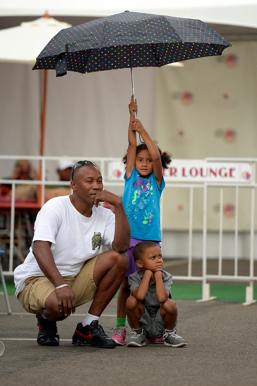 . Ernest Mackey hides under an umbrella held by Saliah Mackey 5, as Xander Mackey checks out Soul X at the Cherry Creek Arts Festival June 7, 2013 in Cherry Creek North. The festival has been going on for three days during the July 4th holiday weekend since 1991, Colorado\'s signature cultural event. (Photo By John Leyba/The Denver Post)