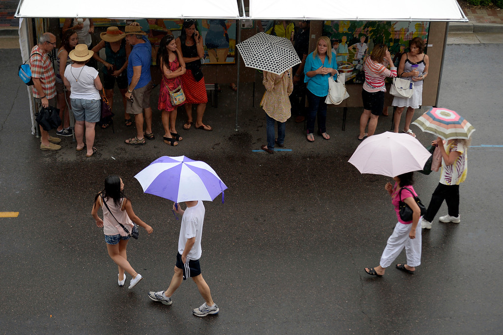 . Patrons take cover as a rain drizzle hits the Cherry Creek Arts Festival June 7, 2013 in Cherry Creek North. The festival has been going on for three days during the July 4th holiday weekend since 1991, Colorado\'s signature cultural event. (Photo By John Leyba/The Denver Post)