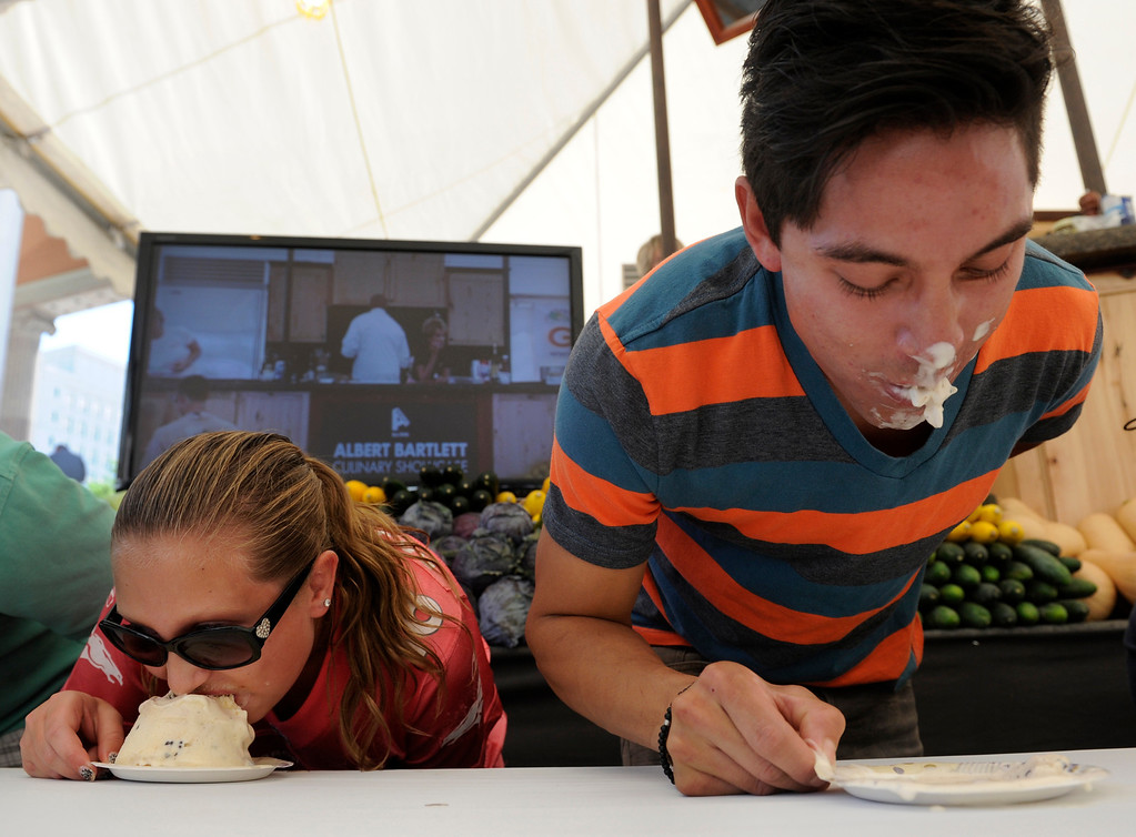 . Justine Haines, 12, left, and Ulysis Baltazar, show their speed-eating talents in the ice cream-eating contest in the culinary showcase tent. Baltazar won the contest and took his free movie tickets on Monday, September 2, 2013. More than 50 Colorado restaurants and food establishments gather at Civic Center Park in Denver for the 30th annual A Taste of Colorado for its final day for 2013. Thousands attend the four day free admission festival held over the Labor Day weekend featuring various types of cuisine as well as live music and entertainment and events for kids.   (Photo By Kathryn Scott Osler/The Denver Post)