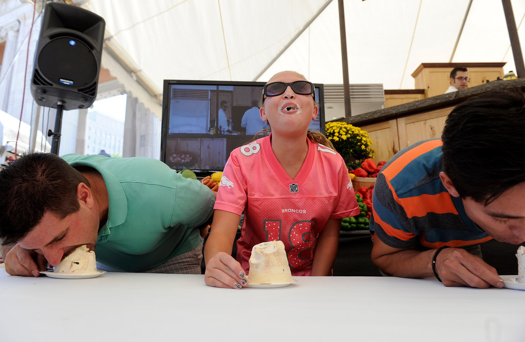 . Ken Aiello, left, Justine Haines, 12, and Ulysis Baltazar, right, show their speed-eating talents in the ice cream-eating contest in the culinary showcase tent. Baltazar won the contest and took his free movie tickets on Monday, September 2, 2013. More than 50 Colorado restaurants and food establishments gather at Civic Center Park in Denver for the 30th annual A Taste of Colorado for its final day for 2013. Thousands attend the four day free admission festival held over the Labor Day weekend featuring various types of cuisine as well as live music and entertainment and events for kids.   (Photo By Kathryn Scott Osler/The Denver Post)