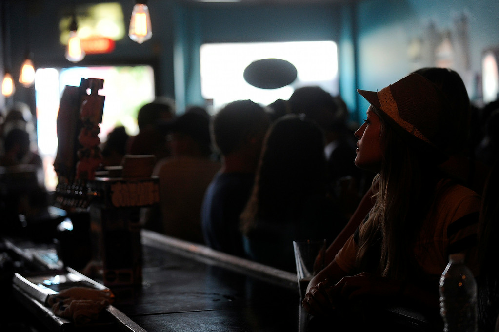 . A patron orders a drink from the bar as In the Whale performs at the Hi-Dive during the Underground Music Showcase on July 27, 2014 in Denver, Colorado. (Photo by Seth McConnell/The Denver Post)