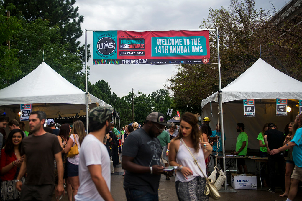 . People walk by the entrance to the Underground Music Showcase main stage along South Broadway during the Annual Underground Music Showcase on Friday, July 25, 2014 in Denver, Colorado.  (Photo by Kent Nishimura/The Denver Post)