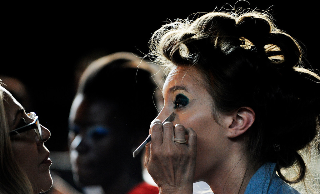 . DENVER, CO. AUGUST 23: Urban Nights a fashion show and auction benefiting the Urban Peak on Friday August 23, 2013 was  held underneath the W. Colfax Ave Viaduct at Mile High Station. Gina Comminello, left, does the make up of model Emma Reins before the show. (Photo By Cyrus McCrimmon/The Denver Post )