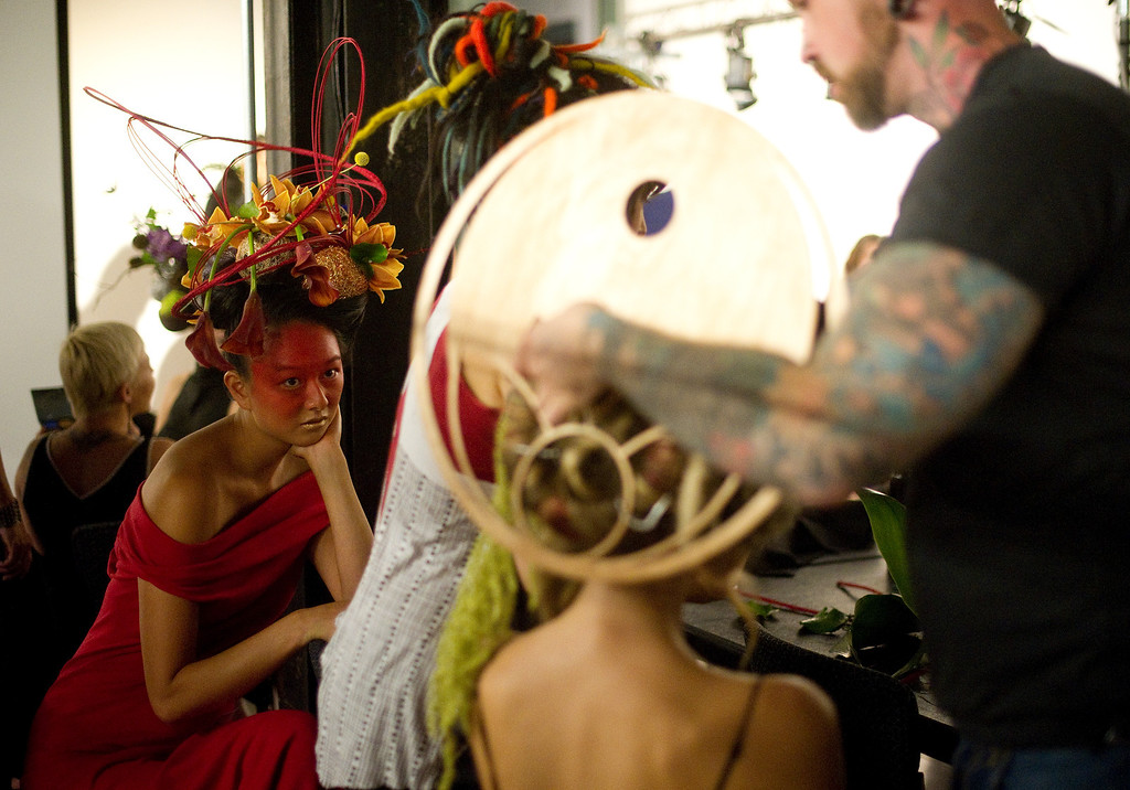 . DENVER, CO - SEPTEMBER 6:  Model Catina Shoemaker, left, watches as  Arthur Williams, right, works on one of his floral head piece creations on the backstage at the Fashion Group International of Denver\'s Rising Star 2013 fashion show on Friday September 6, 2013  at the McNichols Building in Denver. Shoemaker had already received her hair piece from Williams. (Photo By Cyrus McCrimmon/The Denver Post )