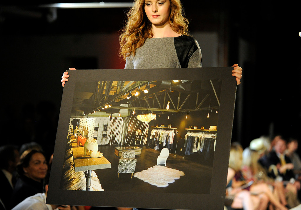 . DENVER, CO - SEPTEMBER 6:   A model carries an image of the work of Vanessa Barcus of Goldyn a finalist at the Fashion Group International of Denver\'s Rising Star 2013 fashion show on Friday September 6, 2013  at the McNichols Building in Denver. (Photo By Cyrus McCrimmon/The Denver Post )