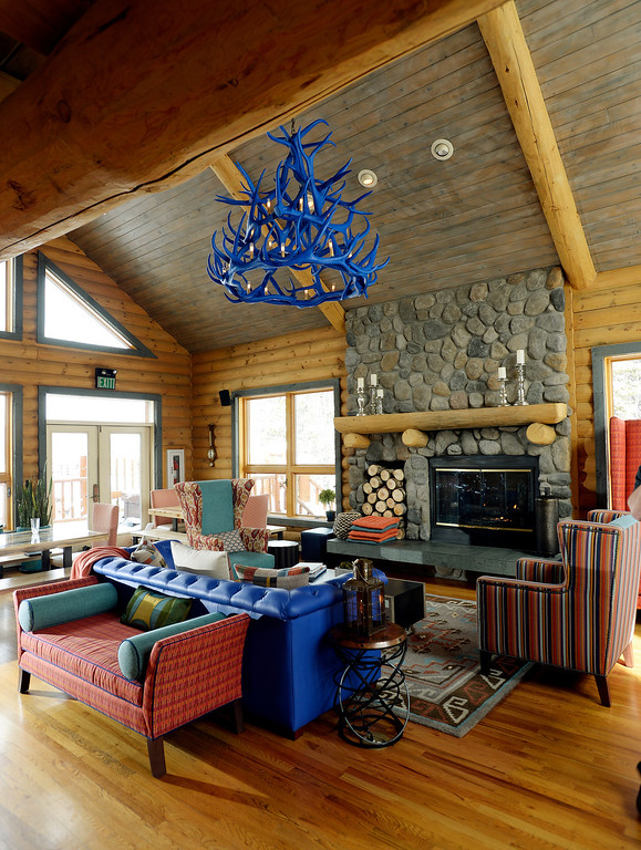 . Edison bulbs glow in the electric blue antler chandelier, a witty re-imagining of a mountain lodge trope at The Bivouac, a newly opened hostel in Breckenridge, Colorado on Tuesday, February 11, 2014. Beneath the chandelier is a matching blue leather sofa and comfortable chairs that face the fireplace and windows that look out onto a snowy landscape. (Denver Post Photo by Cyrus McCrimmon)