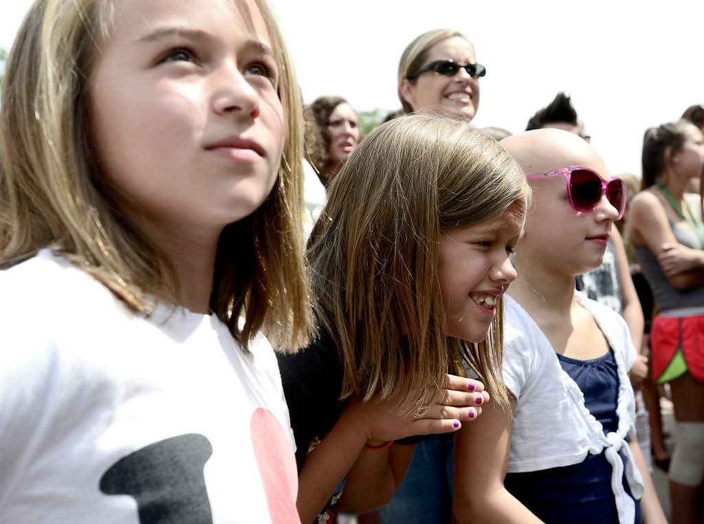 . Reilly Jackson (middle), 9, clasps her hands together in hopes of seeing members of the band One Direction in front of the St. Julian Hotel with her friends Ella Mullins (left), 8 and Presley Ayers (left), 7, in Boulder, Colorado July 24, 2013.  All three girls have tickets to Wednesday night\'s concert in Denver.  DAILY CAMERA/ MARK LEFFINGWELL