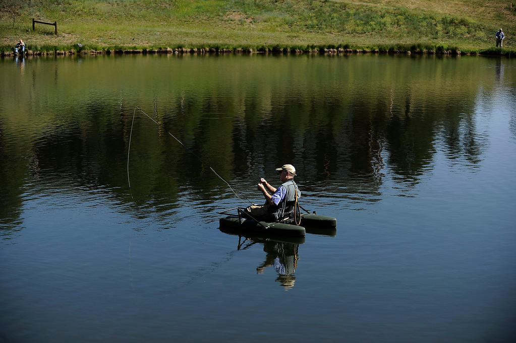 . EVERGREEN, CO - JUNE 21: Larry Norman floats in the middle of Buchanan Pond while fly fishing in Evergreen, Colorado on June 21, 2013. Members of the Evergreen Trout Unlimited are allowed a day of free fishing at the pond for their volunteer service teaching children how to fish. (Photo by Seth McConnell/The Denver Post)