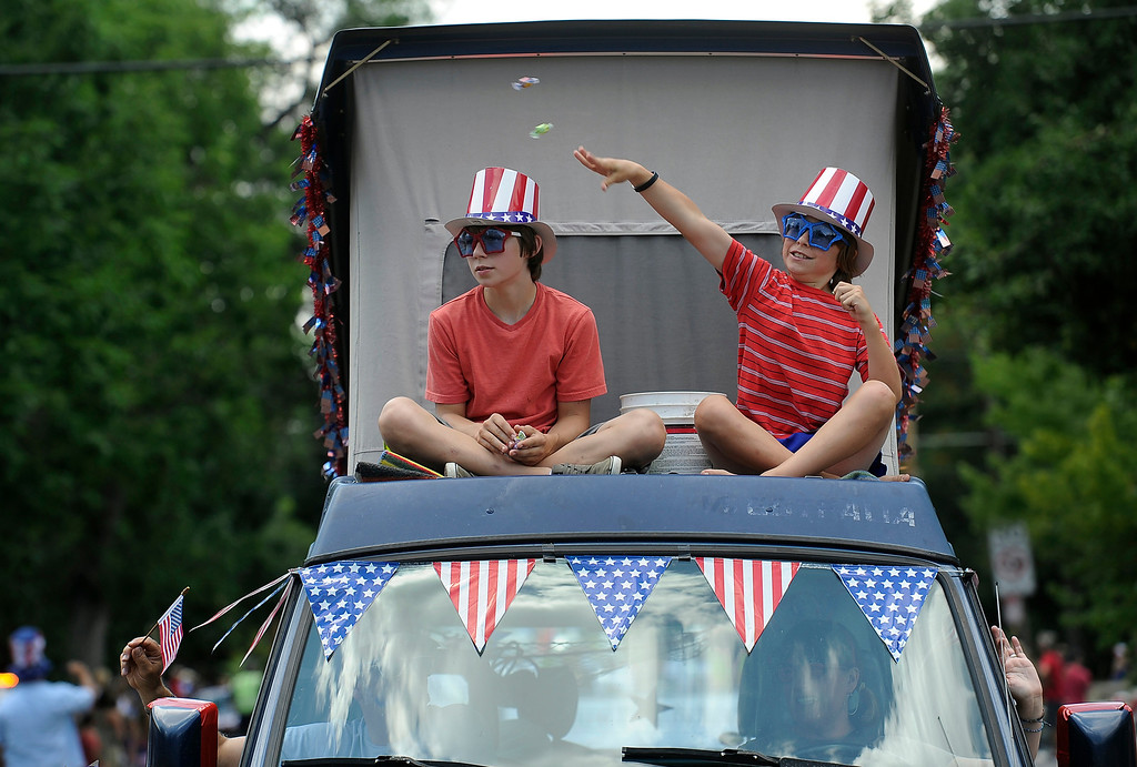 . DENVER, CO - JULY 4: Owen, 13, and brother Wyatt Cooper, 10, toss candy to the crowds gathered to watch the fourth annual Park Hill 4th of July Parade as it winds its way down 23rd Avenue complete with marching bands, neighborhood sponsored floats, bikes and classic cars. (Photo By Kathryn Scott Osler/The Denver Post)