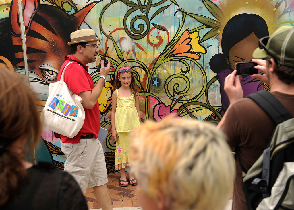 . DENVER, CO. - JULY 5:  Ryan Mandel snapped a picture of his daughter Nevaeh in front of a colorful mural painted by Sam Flores at the Cherry Creek Arts Festival Friday. Cherry Creek Arts Festival opened for the weekend Friday afternoon, July 5, 2013, featuring 250 artists displaying their work. The annual event runs through the weekend. Photo By Karl Gehring/The Denver Post