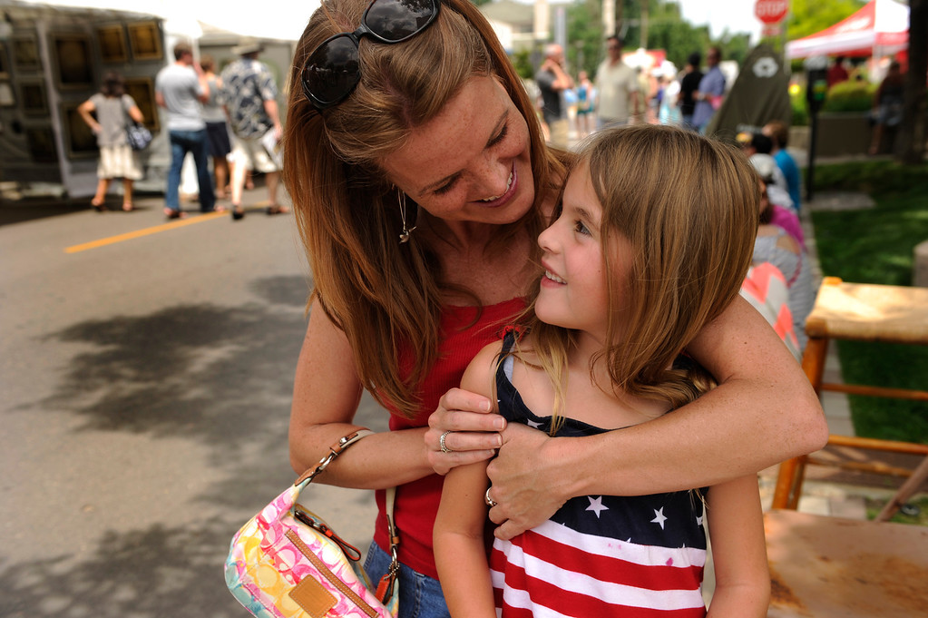. DENVER, CO. - JULY 5:  Courtney Kendall, left, and her niece Piper Kendall, right, took a break in the shade while looking at art at the Cherry Creek Arts Festival Friday. Cherry Creek Arts Festival opened for the weekend Friday afternoon, July 5, 2013, featuring 250 artists displaying their work. The annual event runs through the weekend. Photo By Karl Gehring/The Denver Post