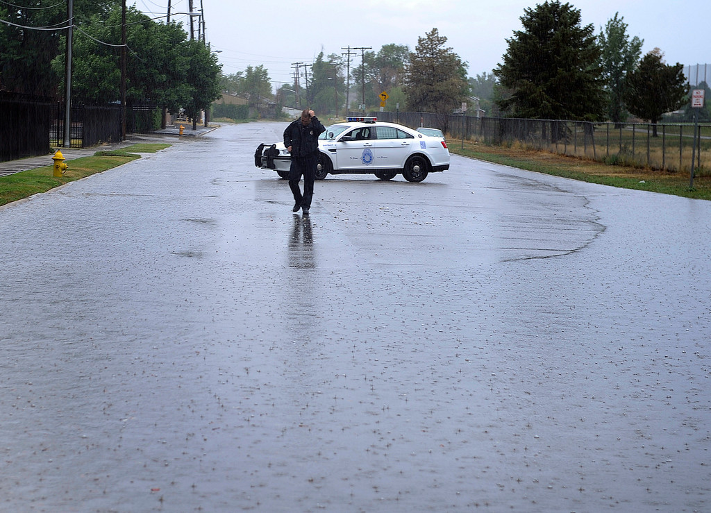 . DENVER, CO. - JULY 13:  A Denver Police officer blocked traffic on Eudora Street north of 39th Avenue after heavy rain fell over Denver Saturday evening, July 13, 2013.  Emergency personnel rescued several people from cars that stalled out in deep water. Photo By Karl Gehring/The Denver Post